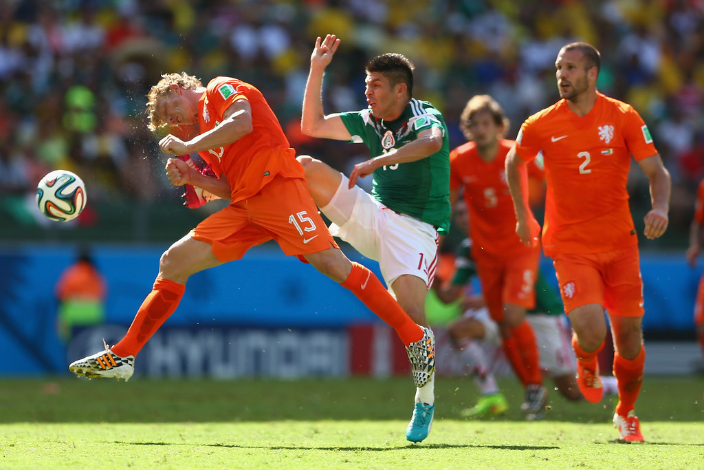 . Dirk Kuyt (L) of Netherlands feels the challenge from Oribe Peralta of Mexico during the 2014 FIFA World Cup Brazil round of 16 match between Netherlands and Holland at Arena Castelao on June 29, 2014 in Fortaleza, Brazil.  (Photo by Michael Steele/Getty Images)