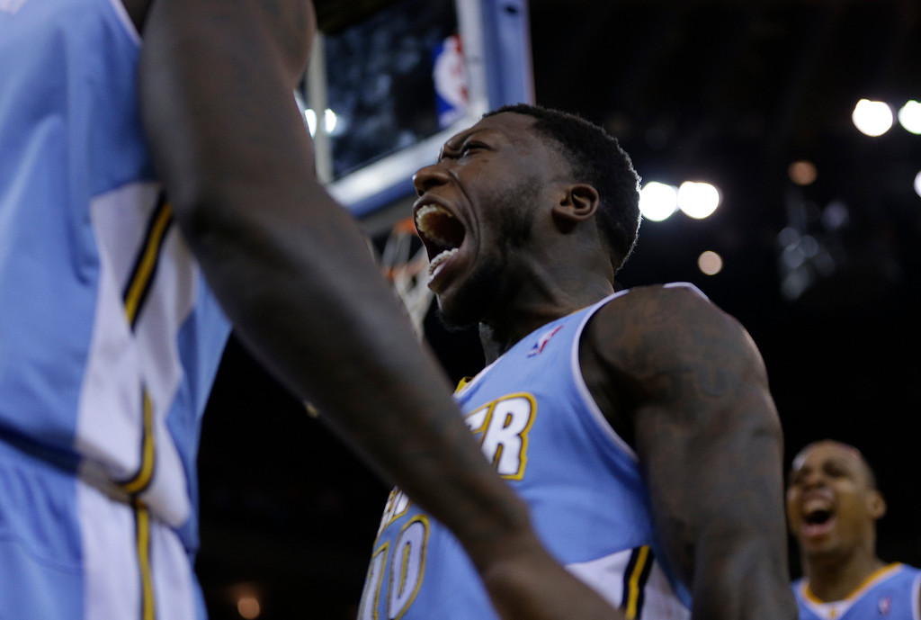 . Denver Nuggets\' Nate Robinson, center, celebrates a score against the Golden State Warriors during the second half of an NBA basketball game on Wednesday, Jan. 15, 2014, in Oakland, Calif. (AP Photo/Ben Margot)