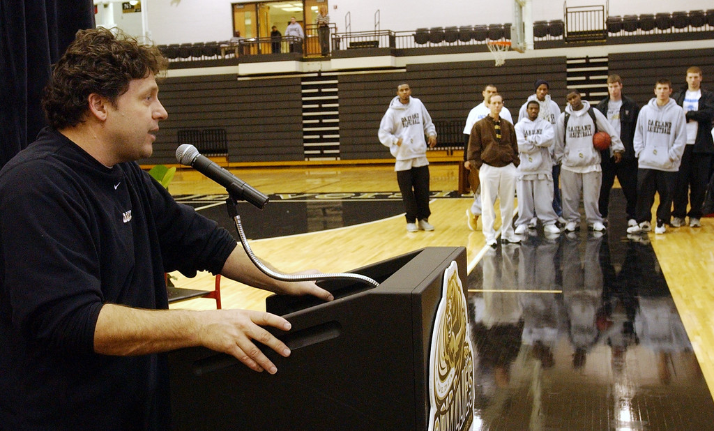 . Oakland University Basketball Head Coach Greg Kampe talks to the media at Oakland University\'s Athletic Center while his team watches from the sidelines. Photographed Wednesday, March 09, 2005.
