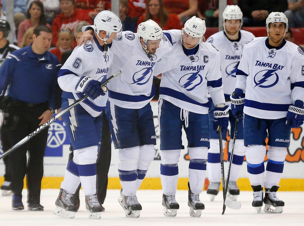 . Tampa Bay Lightning center Cedric Paquette, second from left, is helped from the ice by Anton Stralman (6) and Steven Stamkos (91) in the third period of an NHL hockey game against the Detroit Red Wings, Saturday, March 28, 2015, in Detroit. Detroit won 4-0. (AP Photo/Paul Sancya)