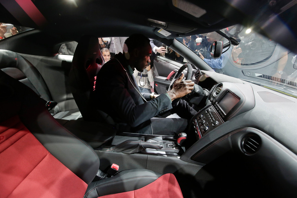 . Olympic gold medalist, Usain Bolt sits in  the 2015 Nissan GT-R is debuted at the Los Angeles Auto Show in Los Angeles, Wednesday, Nov. 20, 2013. (AP Photo/Chris Carlson)