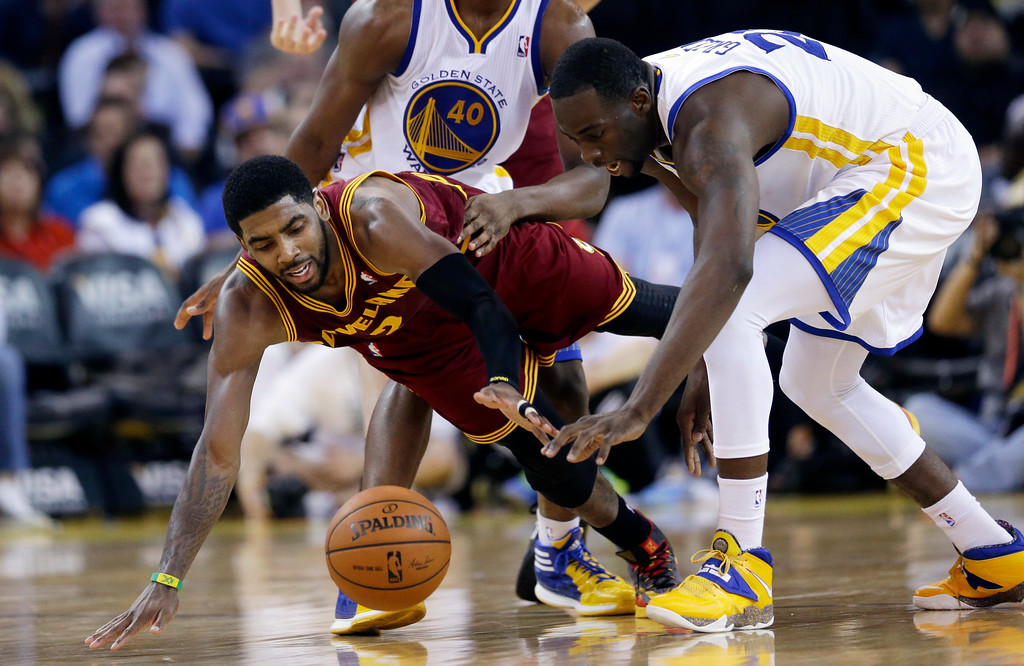 . Cleveland Cavaliers guard Kyrie Irving, left, dives for a loose ball next to Golden State Warriors forward Draymond Green during the second half of an NBA basketball game on Friday, March 14, 2014, in Oakland, Calif. Cleveland won 103-94. (AP Photo/Marcio Jose Sanchez)