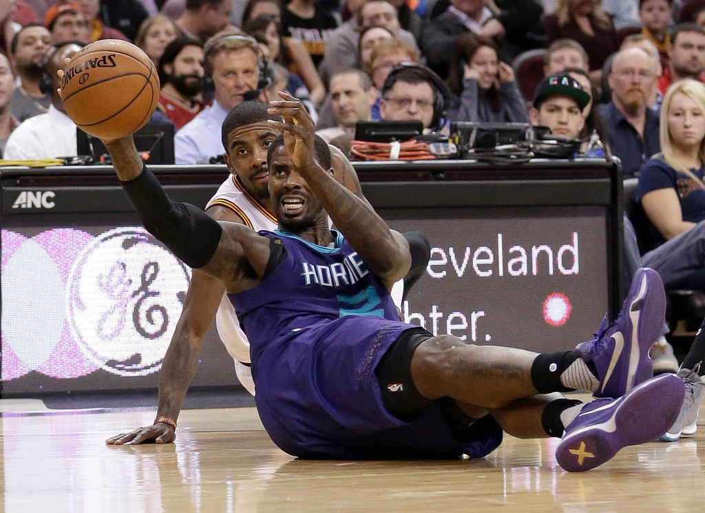 . Charlotte Hornets\' Marvin Williams, front, passes the ball as Cleveland Cavaliers\' Kyrie Irving watches in the first half of an NBA basketball game Wednesday, Feb. 24, 2016, in Cleveland. (AP Photo/Tony Dejak)