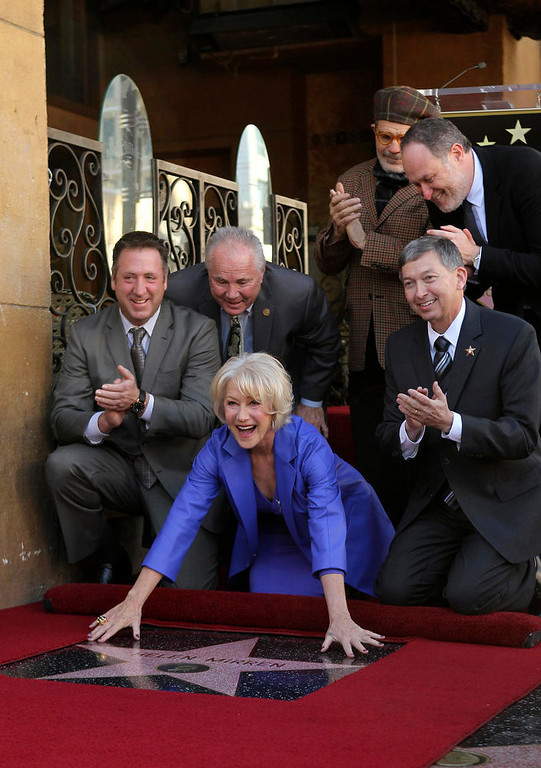 ". Helen Mirren (ground C) reacts as her star, the 2,488th star on the Hollywood Walk of Fame, is unveiled in Hollywood, California, January 3, 2013. The multi major award-winning actress was recently nominated for a Golden Globe Award by the Hollywood Foreign Press Association for Best Actress in a Motion Picture: Drama and for a Screen Actors Guild Award for Best Actress in a Motion Picture Drama. Mirren will appear in the HBO biopic ""Phil Spector\"" later this year.   REUTERS/David McNew"