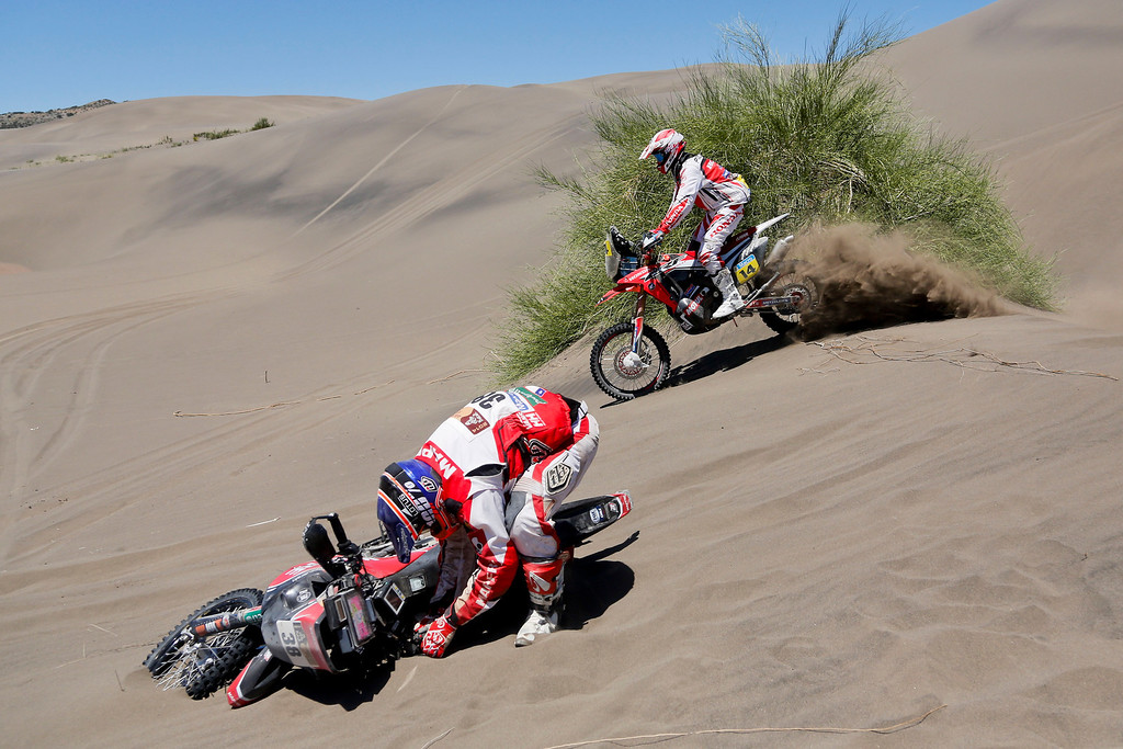 . Speedbrain rider Jeremias Esquerre of Chile lifts his motorcycle after falling as Honda rider Javier Pizzolito, background, rides past him during the second stage of the Dakar Rally between the cities of San Luis and San Rafael in San Rafael, Argentina, Monday, Jan. 6, 2014. The second stage is regarded as one of the fastest in the two-week rally, which ends Jan. 18 in Valparaiso, Chile. (AP Photo/Victor R. Caivano)