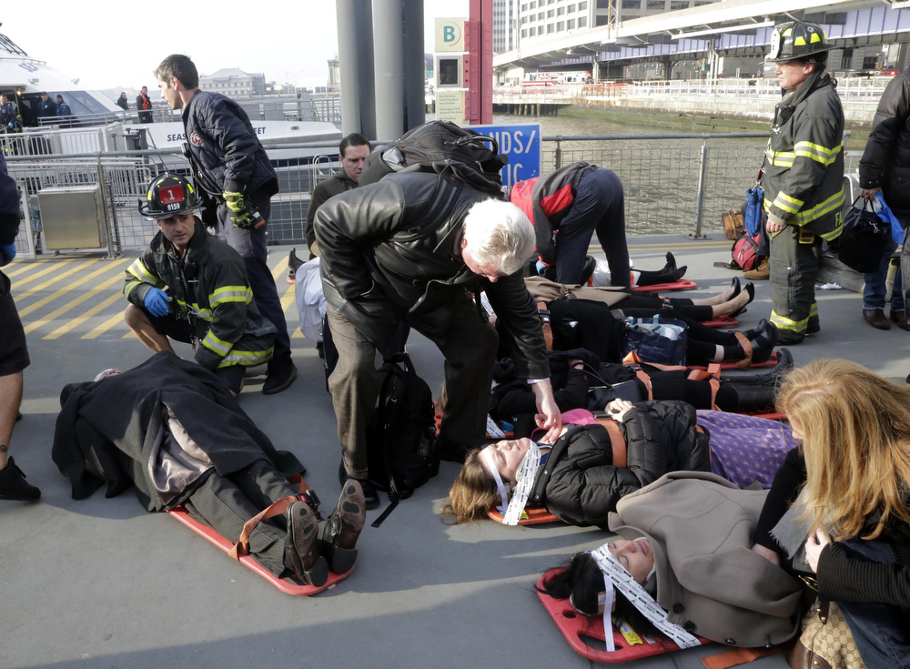 Description of . Injured passengers of the Seastreak Wall Street ferry are aided, in New York,  Wednesday, Jan. 9, 2013. The ferry from Atlantic Highlands, N.J., banged into the mooring as it arrived at South Street in lower Manhattan during morning rush hour, injuring as many as 50 people, at least one critically, officials said.(AP Photo/Richard Drew)