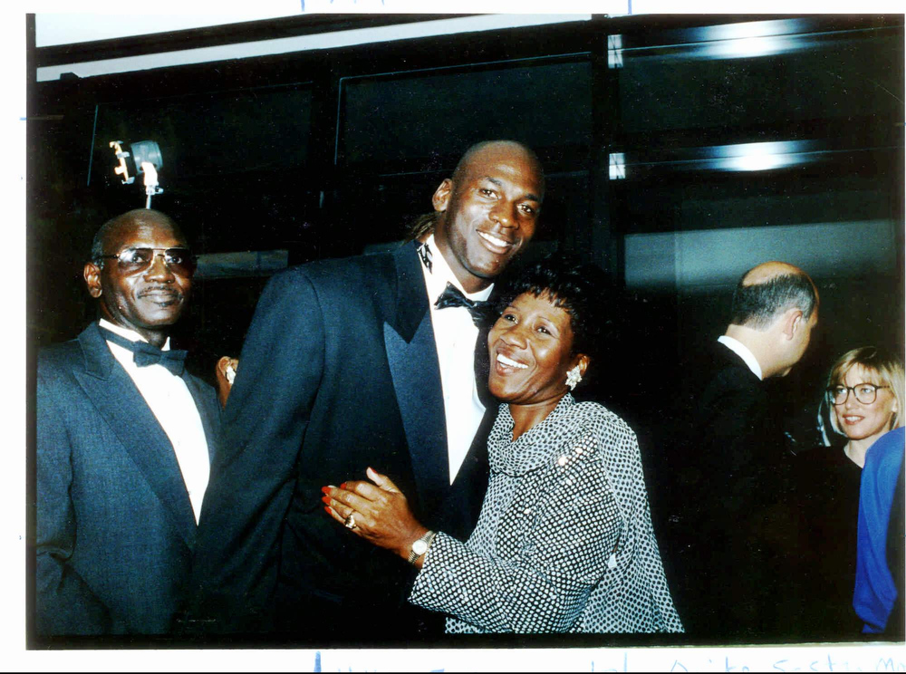 Description of . Chicago Bulls' Michael Jordan hugs his mother, Delores, in this Sept. 15, 1990 file photo as his father, James, looks on, during a gala dinner for the Michael Jordan Foundation at the Hotel Nikko in Chicago. Daniel Green was convicted of murder Thursday, Feb. 29, 1996, in Lumberton, N.C., for the 1993 shooting death of James Jordan. (AP Photo/Chicago Tribune, John Bartley, File)