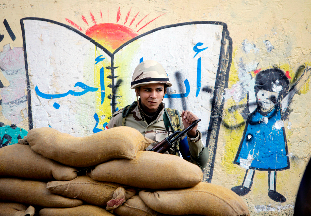 . An Egyptian soldier stands behind protective barrier of sand bags outside a polling station in Cairo, Egypt, Tuesday, Jan. 14, 2014. Egyptians have started voting on a draft for their country\'s new constitution that represents a key milestone in a military-backed roadmap put in place after President Mohammed Morsi was overthrown in a popularly backed coup last July. (AP Photo/Amr Nabil)
