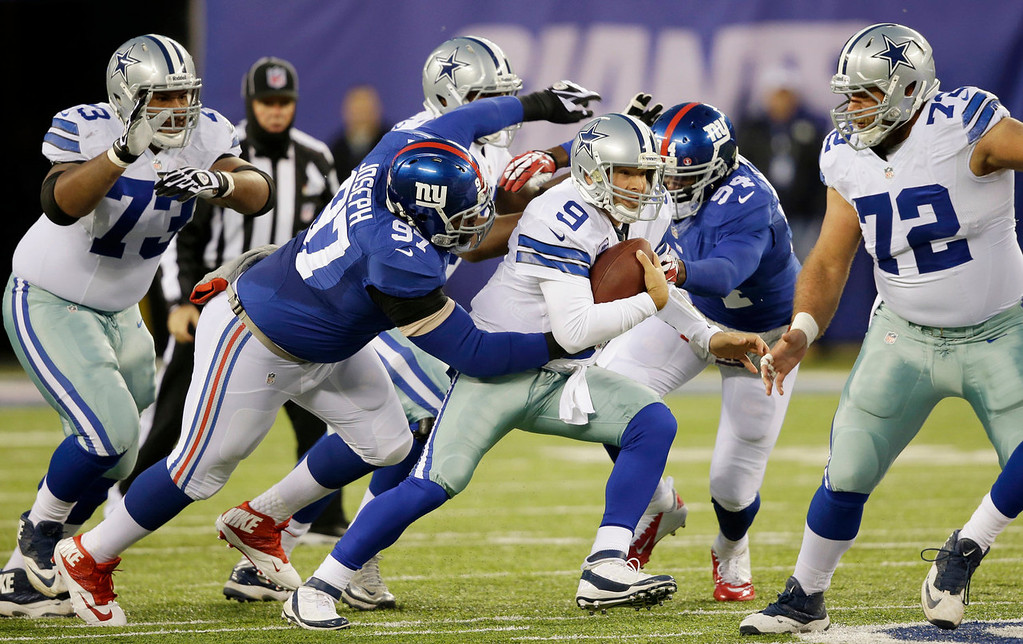 . Dallas Cowboys quarterback Tony Romo (9) is tackled by New York Giants defensive tackle Linval Joseph (97) during the first half of an NFL football game Sunday, Nov. 24, 2013, in East Rutherford, N.J. (AP Photo/Seth Wenig)