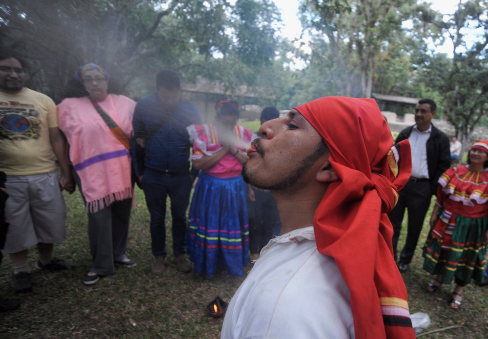 . A Mayan shaman blesses tourists at the archaeological site of the Maya civilization of Copan, Honduras. December 21, 2012. Mystics, hippies and tourists descended on the ruins of Maya cities to mark the close of the 13th bak\'tun - a period of around 400 years - and many hoped it would lead to a better era for humanity. This week, at sunrise on Friday, December 21, an era closes in the Maya Long Count calendar, an event that has been likened by different groups to the end of days, the start of a new, more spiritual age or a good reason to hang out at old Maya temples across Mexico and Central America.  REUTERS/Jorge Cabrera