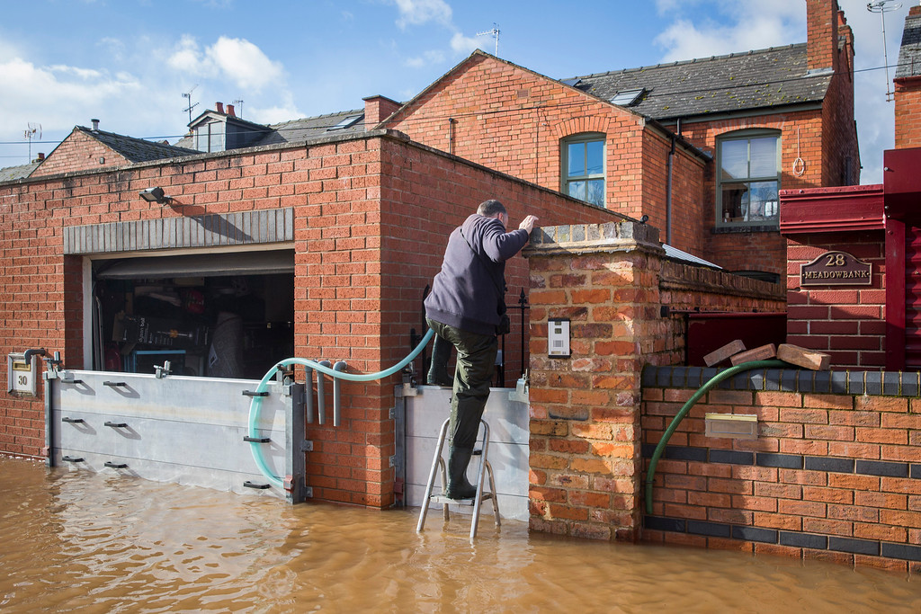 . A man uses a stepladder to climb over flood defences outside his house on Waterworks Road on February 13, 2014 in Worcester, Worcestershire, England. The Environment Agency has issued flood warnings for dozens of areas along the River Severn. (Photo by Rob Stothard/Getty Images)