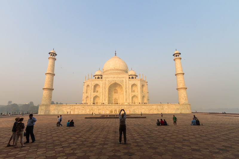 A tourist holds up a phone to take a photo of the Taj Mahal just after sunrise, Agra, India