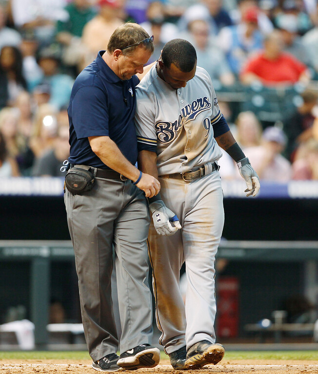 . Milwaukee Brewers head athletic trainer Dan Wright, left, tends to Jean Segura after he hurt his right arm while fouling off a pitch against the Colorado Rockies in the fourth inning of a baseball game in Denver on Saturday, July 27, 2013. Segura remained in the game. (AP Photo/David Zalubowski)