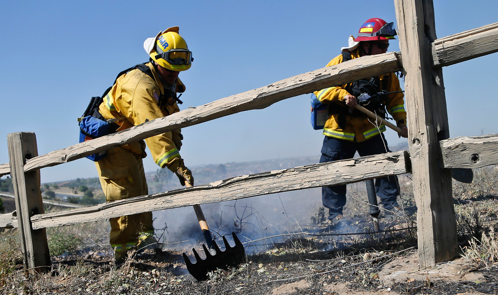 . Firefighters knock out a flare up where a brush fire roared through a section of San Diego\'s north county, Wednesday, May 14, 2014, in San Diego.  Weather conditions that at least temporarily calmed allowed firefighters to gain ground early Wednesday on a pair of wildfires that forced thousands of residents to leave their homes. (AP Photo)