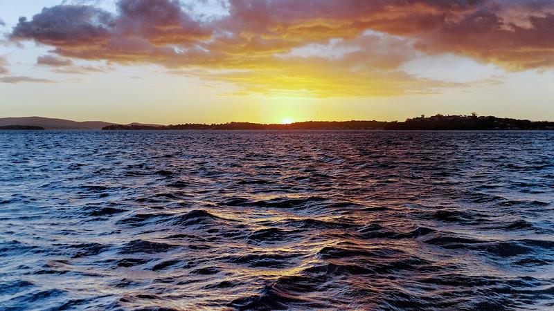 Golden coloured cumulus cloud, coastal sunset seascape.