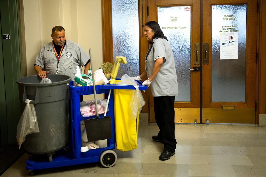 . Custodian Sanjuana Salas pulls her cleaning cart from the elevator as Larry Maldonado stands by at L.A. City Hall. Tuesday, March 18, 2014. (Photo by Michael Owen Baker/L.A. Daily News)
