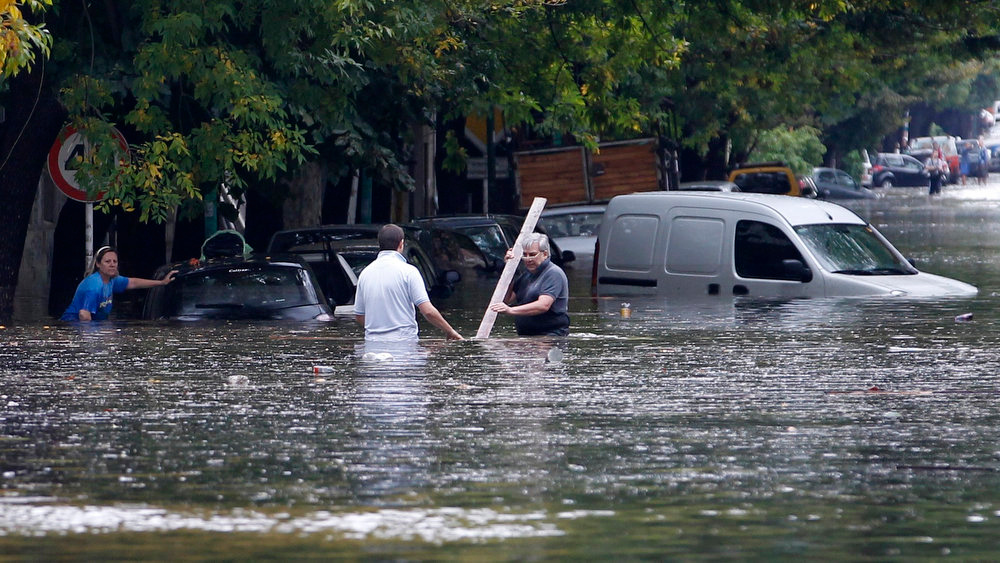 . Men try to remove garbage in flooded street after a rainstorm in Buenos Aires April 2, 2013. Thunderstorms damaged property and vehicles, cut power and caused delays on flights in Buenos Aires and its suburbs. The City\'s SAME emergency service announced that the death toll has risen to five.      REUTERS/Enrique Marcarian