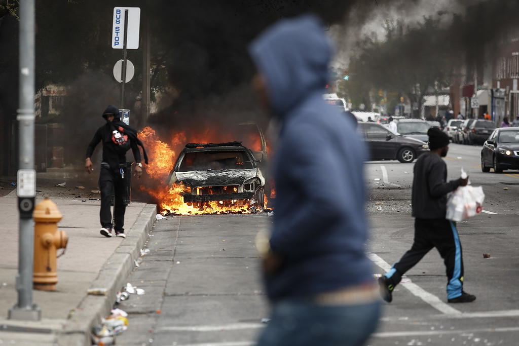 . People walk past burning cars near the intersection of Pennsylvania Avenue and North Avenue, April 27, 2015 in Baltimore, Maryland. Riots have erupted in Baltimore following the funeral service for Freddie Gray, who died last week while in Baltimore Police custody. (Photo by Drew Angerer/Getty Images)