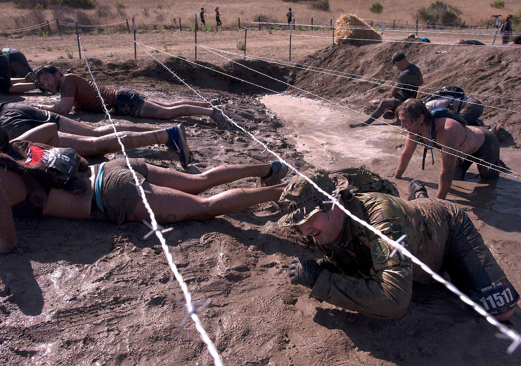 . Some of those who particpated in the grueling Spartan Race, Saturday, August 10th, 2013 crawl through a portion of the almost 13 mile obstacle course.  (Matthew Hintz/Monterey County Herald)