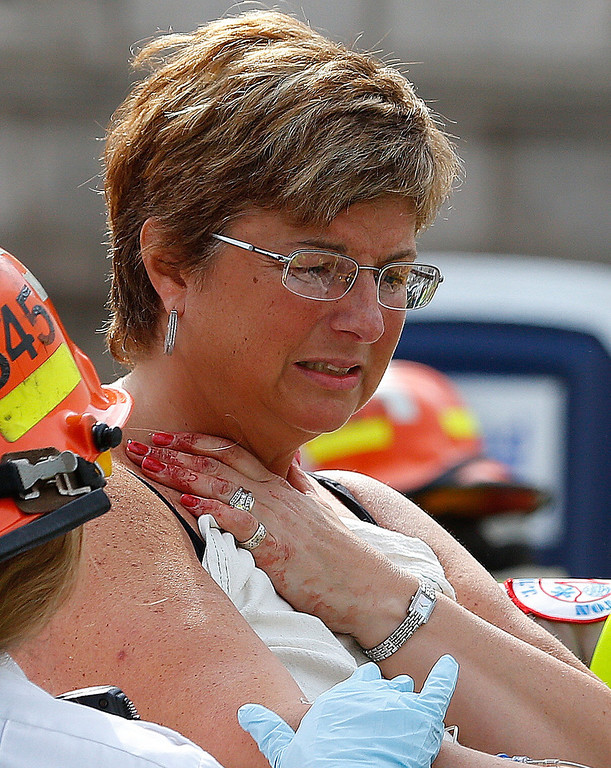 . A woman, with blood on fingers, is loaded into an ambulance after being injured after two bombs exploded on the marathon route on April 15, 2013 in Boston, Massachusetts. Two people are confirmed dead and at least 23 injured after two explosions went off near the finish line to the marathon. (Photo by Jim Rogash/Getty Images)
