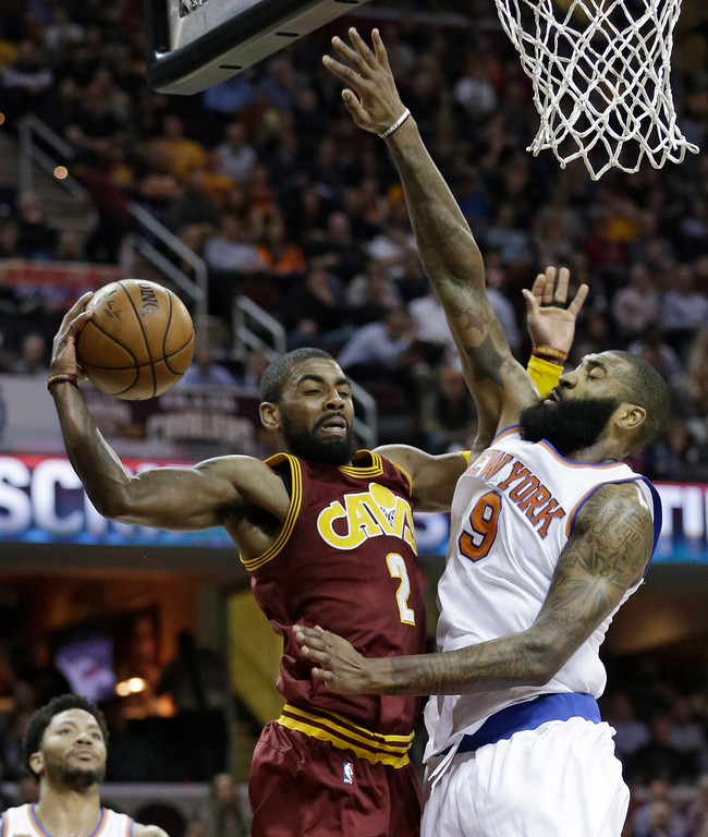 . Cleveland Cavaliers\' Kyrie Irving (2) looks to pass against New York Knicks\' Kyle O\'Quinn (9) in the first half of an NBA basketball game, Thursday, Feb. 23, 2017, in Cleveland. (AP Photo/Tony Dejak)