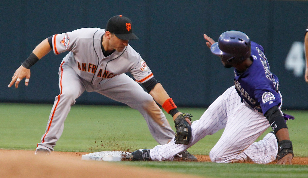 . San Francisco Giants\' Marco Scutaro, left, tags out Colorado Rockies\' Dexter Fowler, right, as he tries to steal second during the first inning of a baseball game, Monday, Aug. 26, 2013, in Denver. Fowler left the game after the play. (AP Photo/Barry Gutierrez)
