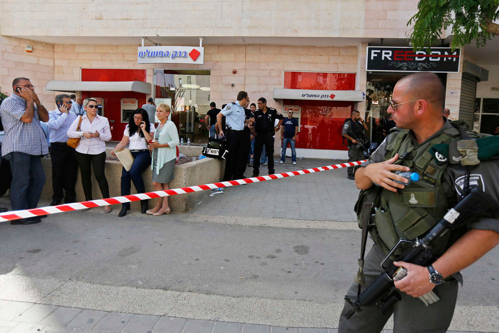 Description of . An Israeli policeman stands guard at the scene of a shooting at a Bank Hapoalim branch in the southern city of Beersheba May 20, 2013. A gunman shot dead four people execution-style in the bank in Israel on Monday after being refused an overdraft and cash from its automatic teller machine. The assailant, identified by media reports as a former paramilitary border policeman, killed himself after police raided the branch to free his hostages. REUTERS/Amir Cohen