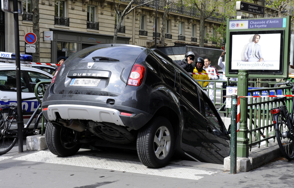 Description of . A car is pictured on April 24, 2012, as it accidentally drove to the stairs of the subway station Chaussee d\'Antin La Fayette, in Paris. French Police cleared the area but many pedestrians came around to have a look at the scene. AFP PHOTO / BERTRAND GUAY