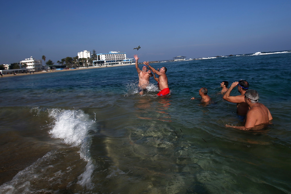 . Swimmers try to catch the cross after it was thrown by an Orthodox priest into the water, during an epiphany ceremony to bless the sea waters at Famagousta or Varosia beach with the abandon hotels, are seen in the background, in the Turkish Cypriots breakaway north part of the eastern Mediterranean divided island of Cyprus, Friday, Jan 6, 2017. Many Orthodox Christian faithful attended the Epiphany Day blessing of the waters in Famagusta in Cyprus\', the second time the ceremony has taken place since 1974 when the small island nation was cleaved along ethnic lines. (AP Photo/Petros Karadjias)