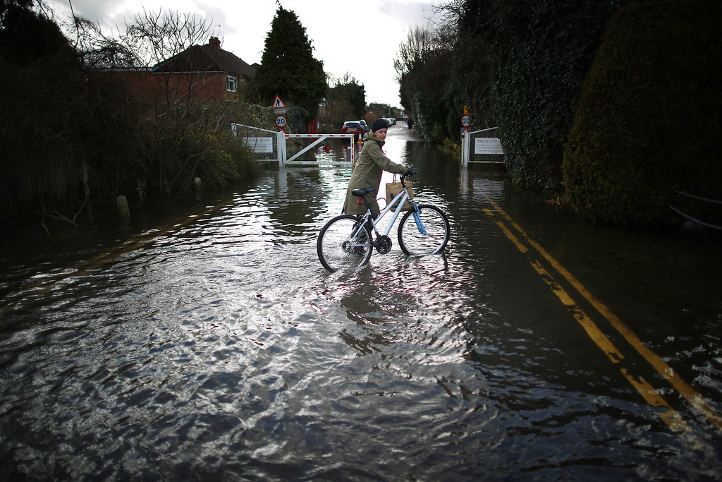 . A resident pushes her bike through flood water on February 13, 2014 in Staines-Upon-Thames, England. Flood water has remained high in some areas and high winds are causing disruption to other parts of the UK with the Met Office issuing a red weather warning.  (Photo by Peter Macdiarmid/Getty Images)