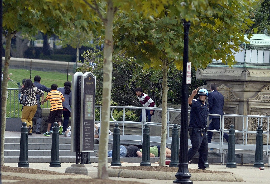 """. People take cover as gun shoot being heard at the Capitol in Washington, DC, on October 3, 2013. The US Capitol was placed on security lockdown Thursday after shots were fired outside the complex, senators said. \""""Shots fired outside the Capitol. We are in temporary lock down,\"""" Senator Claire McCaskill said on Twitter. Police were seen running within the Capitol building and outside as vehicles swarmed to the scene. AFP Photo/Jewel  SAMAD/AFP/Getty Images"""