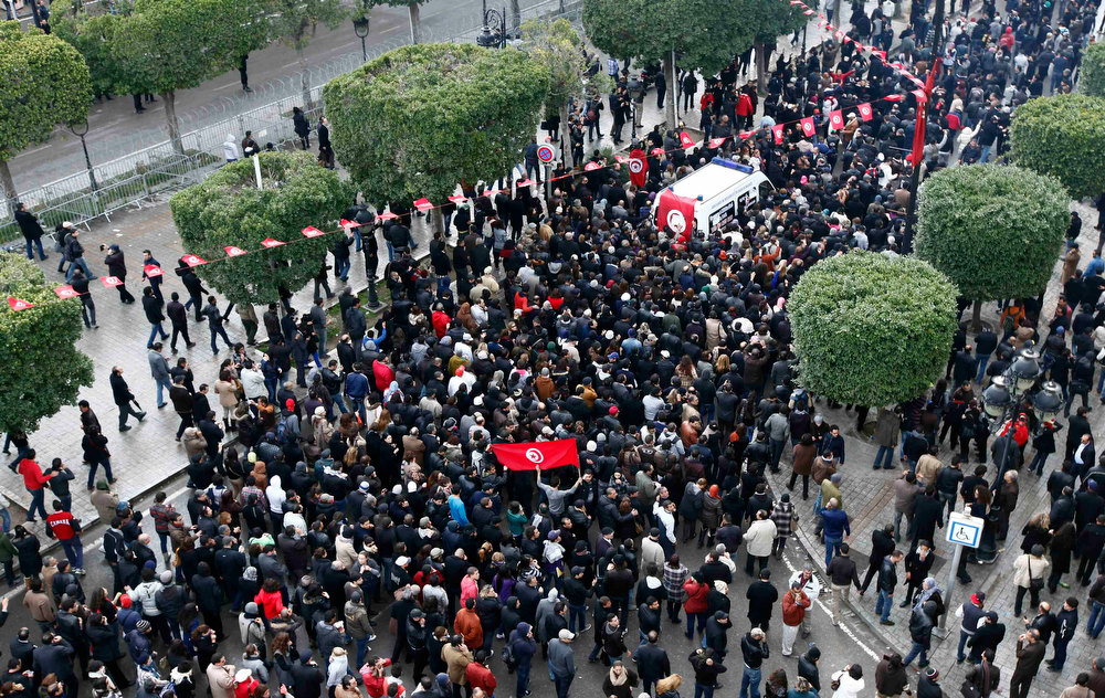 Description of . The body of Tunisian opposition Chokri Belaid (top R) arrives amidst tens of thousands of protesters as they demonstrate on Avenue Habib Bourguiba in Tunis February 6, 2013. Tunisia's secular opposition Popular Front said it was pulling out of the constituent assembly charged with writing a constitution after an opposition politician was killed on Wednesday. REUTERS/Anis Mili
