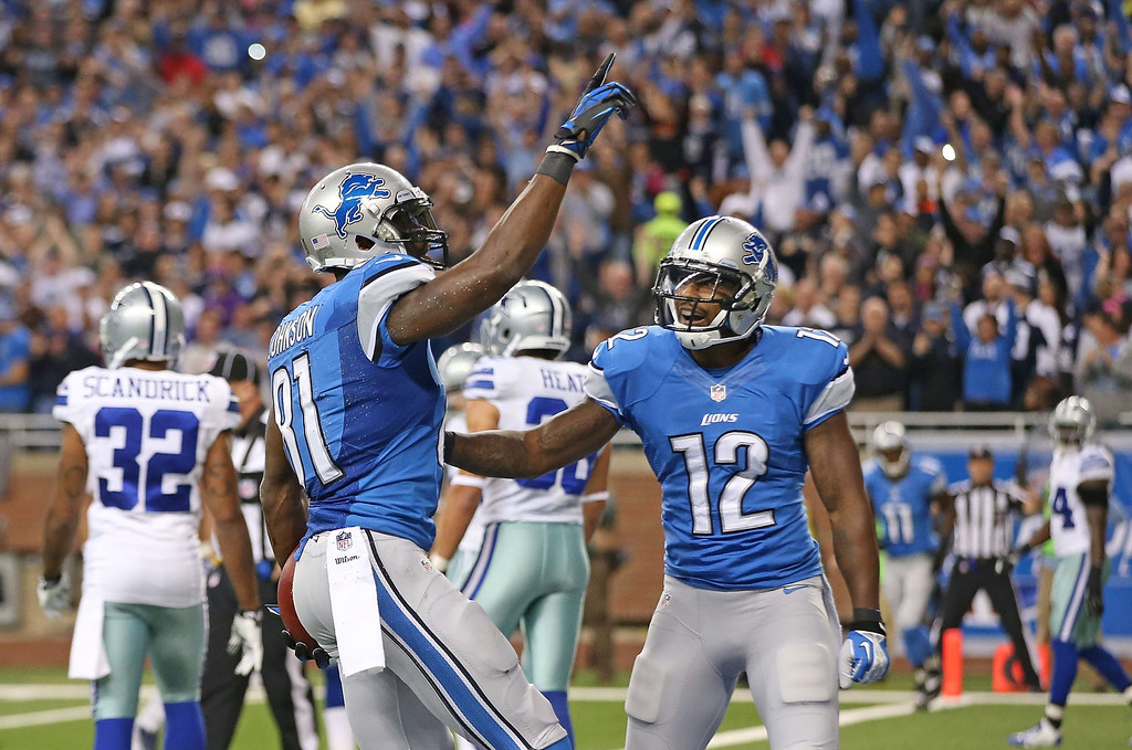 . Calvin Johnson #81 of the Detroit Lions celebrates with teammate Jeremy Ross #12 after scoring a first quarter touchdown during the game against the Dallas Cowboys at Ford Field on October 27, 2013 in Detroit, Michigan.  (Photo by Leon Halip/Getty Images)