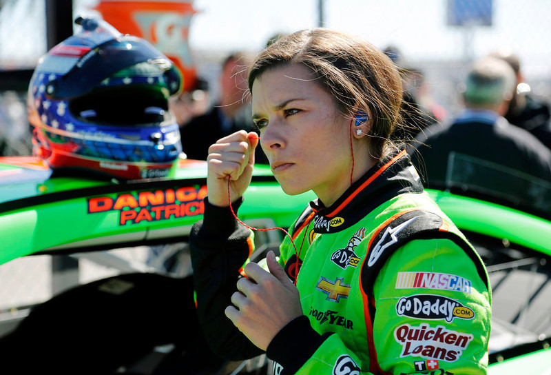 . Danica Patrick removes her earplugs by her car on pit road after qualifying for the NASCAR Daytona 500 Sprint Cup Series auto race at Daytona International Speedway, Sunday, Feb. 17, 2013, in Daytona Beach, Fla. Patrick won the pole, becoming the first woman to secure the top spot for any Sprint Cup race. (AP Photo/Terry Renna)