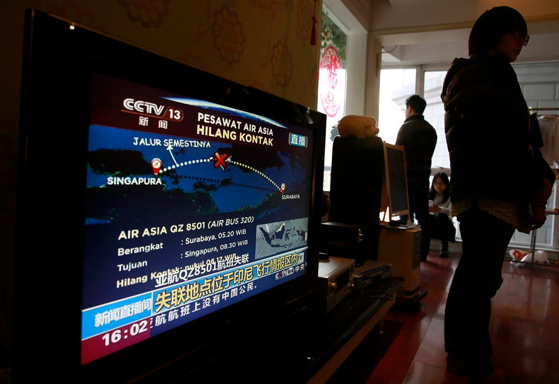 . Relatives of the passengers on board the Malaysia Airlines Flight 370 that went missing on March 8, 2014 stand near a TV showing a live broadcast of the missing AirAsia Flight 8501 from Surabaya to Singapore, during their year-end gathering at a house in Beijing, China Sunday, Dec. 28, 2014. In the third air incident connected to Malaysia this year, an AirAsia plane disappeared Sunday while flying over the Java Sea after taking off from Indonesia\'s second-largest city for Singapore. (AP Photo/Andy Wong)