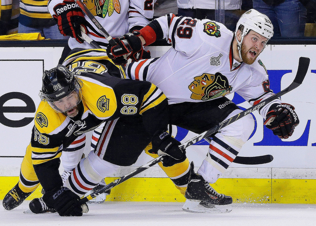 . Boston Bruins right wing Jaromir Jagr (68), of the Czech Republic, ties up Chicago Blackhawks left wing Bryan Bickell (29) during the third period in Game 3 of the NHL hockey Stanley Cup Finals in Boston, Monday, June 17, 2013. The Bruins won 2-0. (AP Photo/Elise Amendola)