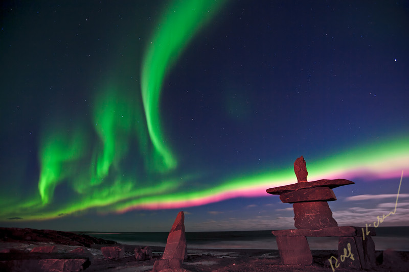 Northern Lights, Aurora borealis, above an inukshuk near the town of Churchill, Hudson Bay, Manitoba, Canada.