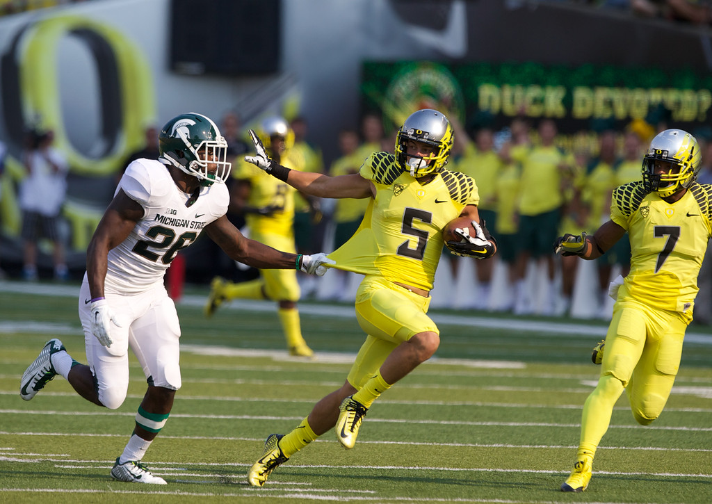 . Oregon Ducks Devon Allen eludes tackle on his way to a second quarter touchdown against the Michigan State Spartans at Autzen Stadium, in Eugene, Oregon, Sat, Sept. 6, 2014.     (AP Photo/The Oregonian, Thomas Booyd)  MAGS OUT; TV OUT; LOCAL TELEVISION OUT; LOCAL INTERNET OUT; THE MERCURY OUT; WILLAMETTE WEEK OUT; PAMPLIN MEDIA GROUP OUT