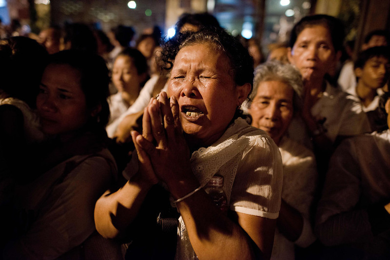 . Cambodian mourners cry and pray as smoke rises out from the roof the crematorium during the cremation where a coffin bearing the remains of Cambodia\'s late King Norodom Sihanouk is placed, near the Royal Palace in Phnom Penh on February 4, 2013. Thousands of mourners massed in the Cambodian capital as the kingdom cremated its revered former King Norodom Sihanouk, who steered his country through six turbulent decades. AFP PHOTO/ Nicolas ASFOURI/AFP/Getty Images
