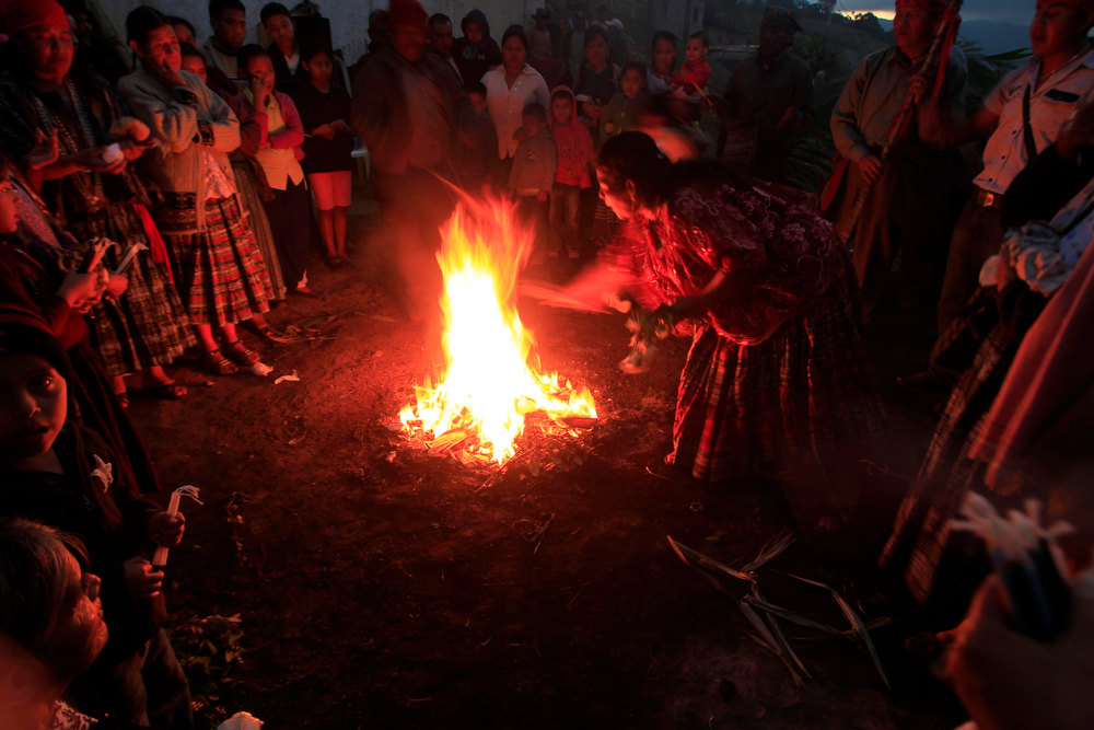 Description of . A woman burns candles in the sacred fire during the pre-Hispanic mass of