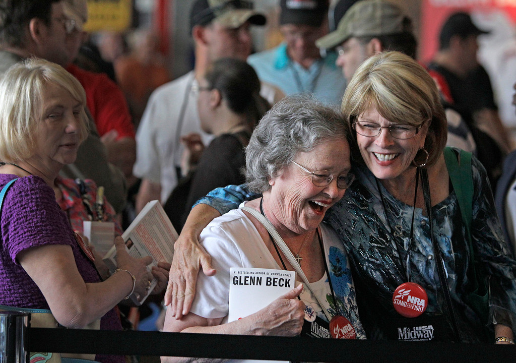. Eby Owen, center, of Dunedin, Fla., and Debbie Brinson, right, of San Antonio share a hug as they wait in line for the Glenn Beck book signing event during the NRA convention at the George R. Brown Convention Center  Saturday, May 4, 2013, in Houston. National Rifle Association leaders told members Saturday that the fight against gun control legislation is far from over, with battles yet to come in Congress and next year\'s midterm elections, but they vowed that none in the organization will ever have to surrender their weapons. (AP Photo/Houston Chronicle,  Melissa Phillip)