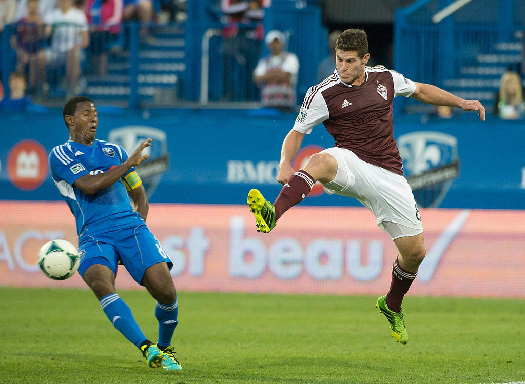 . Montreal Impact\'s Patrice Bernier pulls back as Colorado Rapids\' Dillon Powers jumps in for the ball during the second half of an MLS soccer game in Montreal on Saturday, June 29, 2013. (AP Photo/The Canadian Press, Peter McCabe)