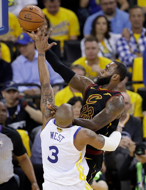 . Cleveland Cavaliers forward LeBron James, right, shoots against Golden State Warriors forward David West during the first half of Game 1 of basketball\'s NBA Finals in Oakland, Calif., Thursday, May 31, 2018. (AP Photo/Marcio Jose Sanchez)