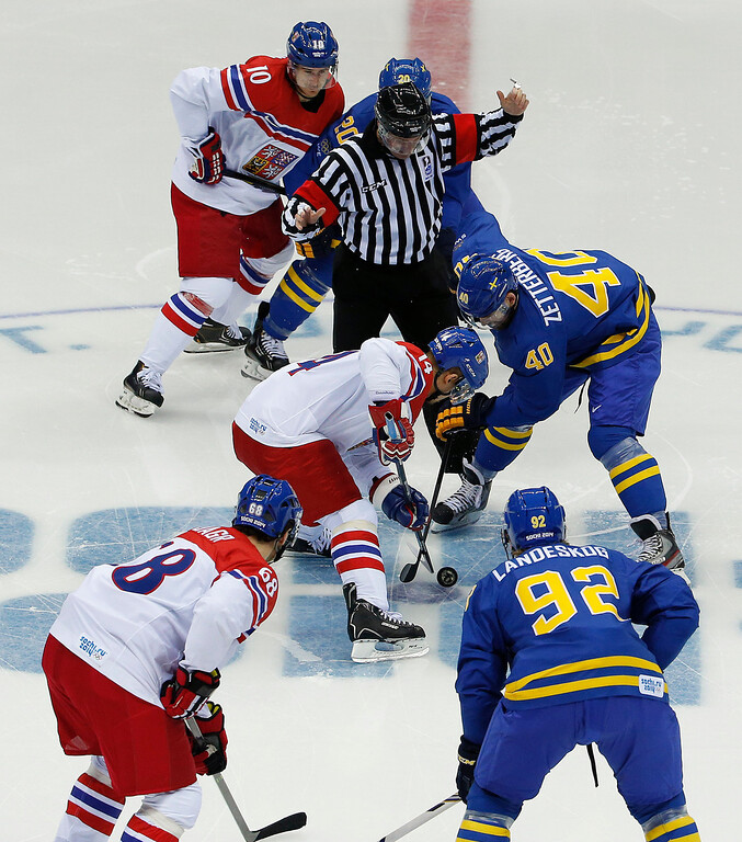 . Players from the Czech Republic and Sweden face off at the start of a men\'s ice hockey game at the 2014 Winter Olympics, Wednesday, Feb. 12, 2014, in Sochi, Russia. (AP Photo/Julio Cortez)