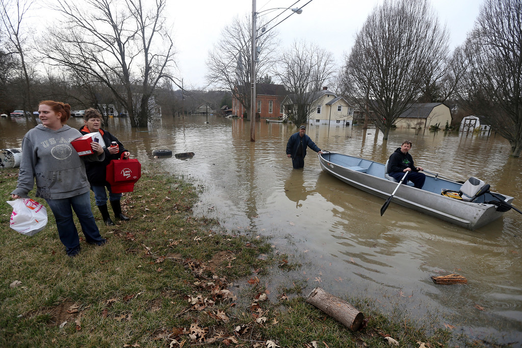 . From left, Lori Sullender, Lisa Tomlin, William Michael Sullender Jr. and Fred Sullender pull items out of homes Sunday, Feb. 25, 2018, in Cincinnati. Heavy rains overnight have sent the swollen Ohio River at Cincinnati to its highest point in 20 years with the river expected to remain above flood stage through the end of the week, a National Weather Service meteorologist said Sunday. (Kareem Elgazzar/The Cincinnati Enquirer via AP)