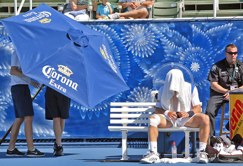 021811 - DELRAY BEACH - Ball kid Billy Earnhart, left, readies the umbrella to provide shade to Swede Mikael Pernfors during Saturday's  action at the 2011 ITC in Delray Beach.  Photo by Tim Stepen