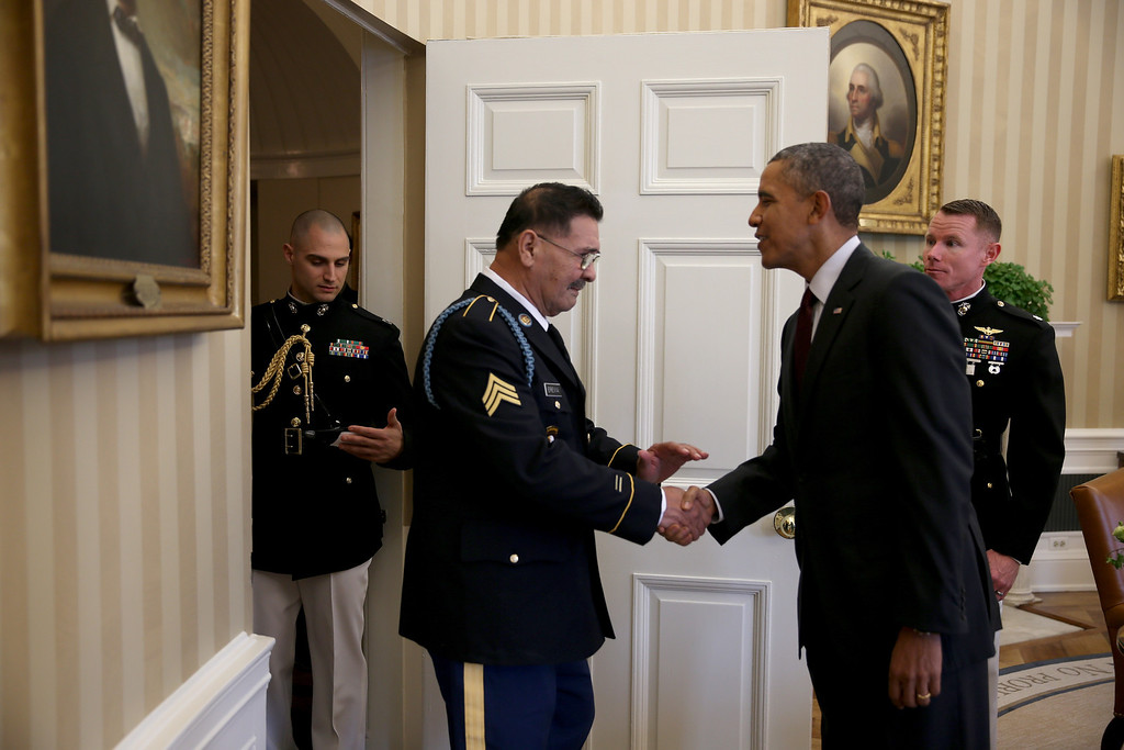 . U.S. President Barack Obama greets  U.S. Army Specialist Four (Ret.) Santiago J. Erevia, a Vietnam War veteran, in the Oval office before presenting him with the Medal of Honor at a ceremony in the White House on March 18, 2014 in Washington, DC.  Erevia, U.S. Army Staff Sgt. (Ret.) Melvin Morris, and U.S. Army Sgt. First Class (Ret.) Jose Rodela were joined by families of 21 others who were presented posthumously with the Medal of Honor for conspicuous gallantry. (Photo by Joe Raedle/Getty Images)