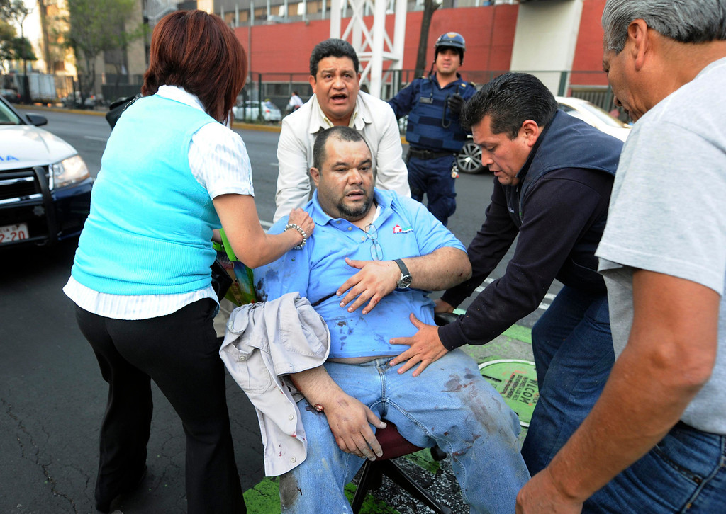 . An injured man is being transported in an office chair outside the headquarters of state oil giant Pemex in Mexico City January 31, 2013. An explosion rocked the Mexico City headquarters of Pemex on Thursday, killing at least 14, injuring more than 100 others and causing extensive damage to the building. The blast, which media reports said was caused by machinery exploding, occurred in the basement, emergency officials said. REUTERS/Alejandro Dias
