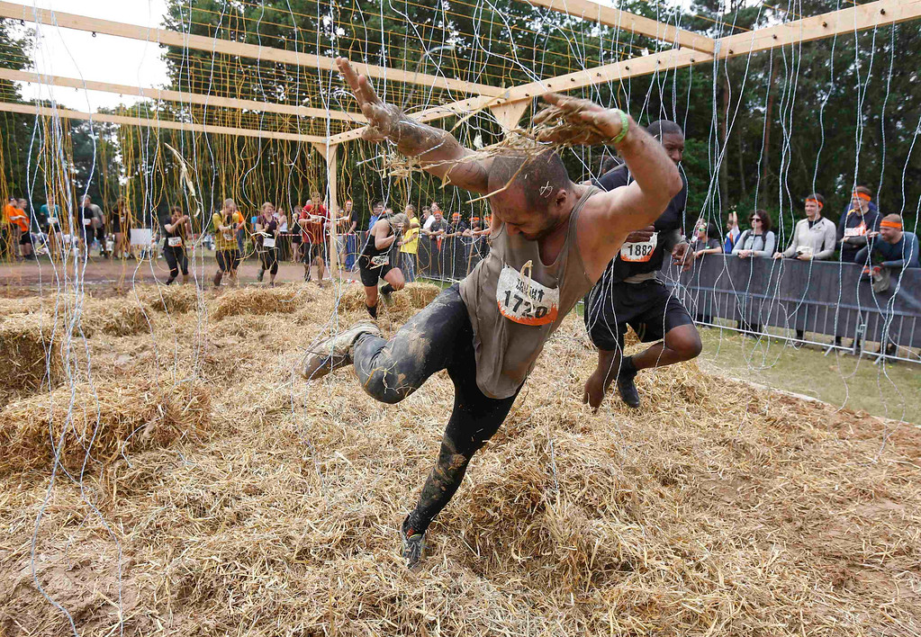 ". A participant of the ""Tough Mudder\"" endurance event series struggles in the \""Electroshock Therapy\"" obstacle made of electrical wire holding some 10,000 Volts in the Fursten Forest, a former British Army training ground near the north-western German city of Osnabrueck July 13, 2013. The hardcore but un-timed event over 16 km (10 miles) was designed by British Special Forces to test mental as well as physical strength. Some 4,000 competitors had to overcome obstacles of common human fears, such as fire, water, electricity and heights.   REUTERS/Wolfgang Rattay"