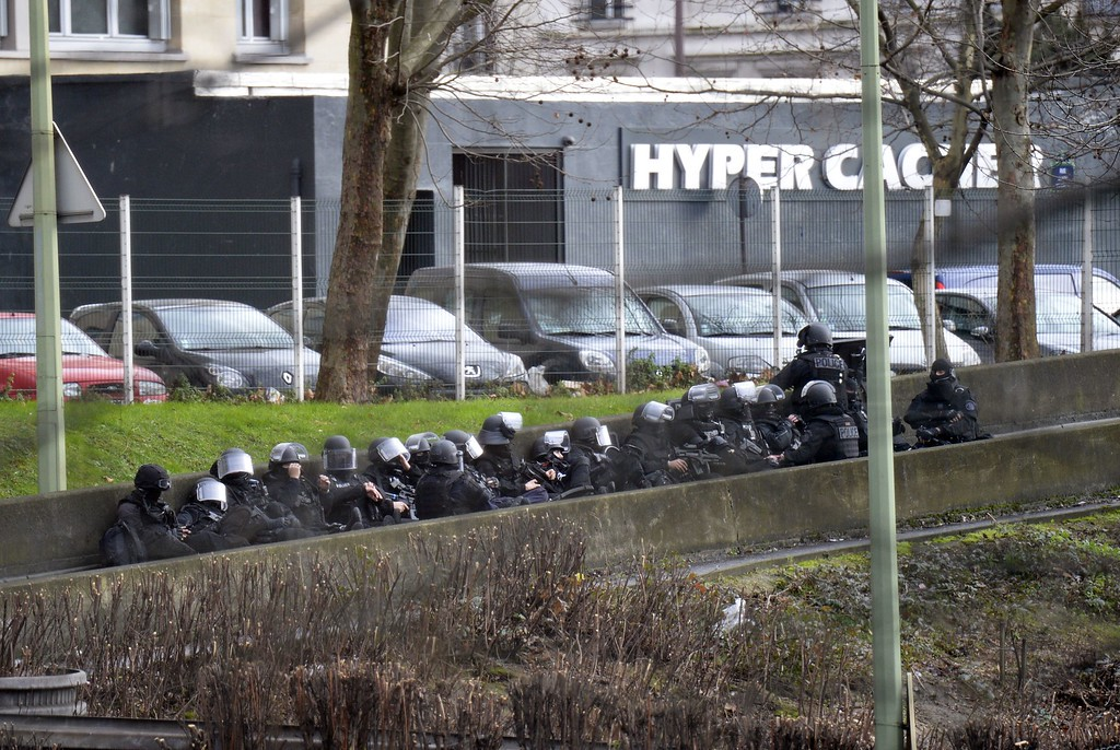. A photo taken on January 9, 2015 shows members of the French police forces taking position by the kosher grocery store in Saint-Mande, near Porte de Vincennes, eastern Paris, where at least one person was injured when a gunman opened fire at the kosher grocery store and took at least five people hostage, sources told AFP. The attacker was suspected of being the same gunman who killed a policewoman in a shooting in Montrouge in southern Paris on January 8. AFP PHOTO / ERIC  FEFERBERG/AFP/Getty Images